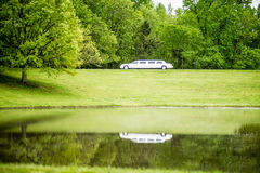 White limo reflecting in lake Stock Image
