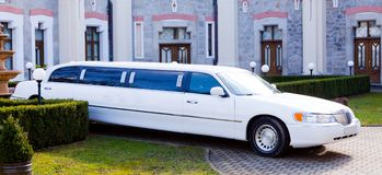 A white limousine. In a garden of a chateau Royalty Free Stock Image