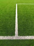 White line on artificial grass field on football playground. Detail of a cross of painted white lines in a soccer field. Stock Image