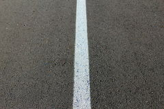 White line on asphalt. White line on black asphalt Royalty Free Stock Photos
