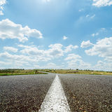 White line on asphalt road under sky with clouds Royalty Free Stock Photo