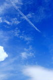 White line cloud hangs in the blue sky. Blue sky and white clouds and white line created by airplane Stock Images