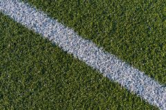 White line on a green artificial soccer field stock images