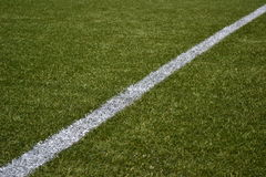 White line on green artificial turf soccer field stock photo