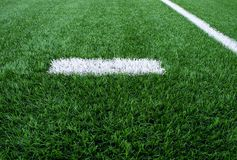 White line marks painted on artificial green turf background. Playground with plastic grass. Royalty Free Stock Images
