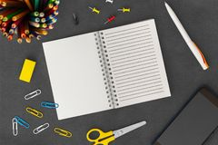 White line spiral paper notebook with mobile phone, pen, colored pencils, eraser, paper clips and scissors on dark background. Open white line spiral paper stock image