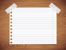 White lined notebook paper sheet, sticked on gray wooden wall, desk Royalty Free Stock Images