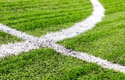 White lines crossing at a football field. White lines of field markings crossing at a football field made of artificial turf Royalty Free Stock Photos