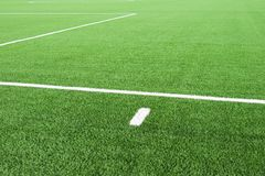 White lines on football playground. Detail of lines in a soccer field. Plastic grass and finely ground black rubber. Stock Photography