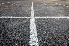 White lines intersect on parking lot. Two white lines intersecting on asphalt floor texture Royalty Free Stock Photo