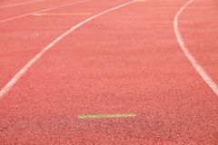 White lines and texture of running racetrack, red rubber racetracks in small stadium Stock Photos