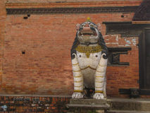 White lion with breast on the background of brickwork. In the historical center of Kathmandu Stock Photos