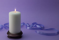 White lit candle with lilac ribbon and background. Studio photo Royalty Free Stock Photo