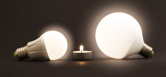 White Little Candle And LED Electric Bulbs On Dark Background. C Royalty Free Stock Image