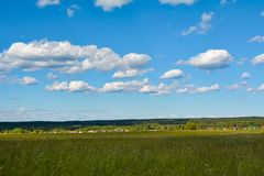 White little clouds float above a green fields. Beautiful landscapes are found in the countryside royalty free stock photography