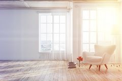 White living room with an armchair toned. Empty white living room interior with a wooden floor, tall windows and a white armchair near a stack of books. 3d Royalty Free Stock Images