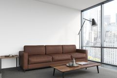 White living room, brown sofa, poster. White living room interior with a brown sofa, a poster hanging above it, a panoramic window and a coffee table. 3d Royalty Free Stock Photo
