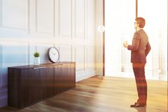White living room corner, cabinet and clock, man. Businessman in a white loft living room interior with a wooden floor, a dark wooden cabinet with a clock on it Royalty Free Stock Photo