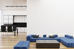 White living room with a blue sofa. White living room corner with a long blue sofa, a square coffee table, and a kitchen. 3d rendering mock up Stock Images