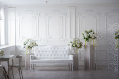 White living room in ekostile. Loft room with flowers, sofa, pillars, screen Royalty Free Stock Images