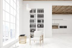 White living room with a bookcase, kitchen Royalty Free Stock Photos