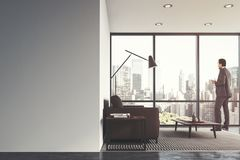 White living room interior, brown sofa, man. White living room interior with a concrete floor, a panoramic window, and a brown sofa near a coffee table. A man Royalty Free Stock Photo