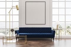 White living room, blue sofa, poster. White living room interior with a wooden floor, loft windows, a blue sofa, a coffee table and a framed vertical poster on a Stock Photos