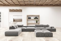 White living room gray sofas. White living room interior with a wooden floor, shelves, several gray sofas and a kitchen in the background. 3d rendering mock up Stock Photo