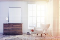 White living room with an armchair, poster toned. White living room interior with a wooden floor, a tall window and a white armchair near a dresser with a poster Royalty Free Stock Photo