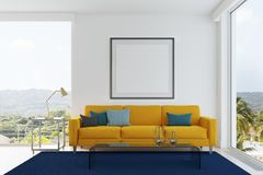 Yellow sofa, blue and green pillows living room. White living room interior with a yellow sofa, gray, blue and black pillows, a blue carpet, a framed square Royalty Free Stock Photography