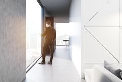 White living room and kitchen, businessman. Businessman in a modern living room interior with white panel and concrete walls, panoramic windows, a soft sofa and Stock Photo
