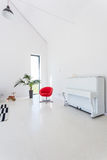 White living room with piano. Image of white and spacious living room with modern red chair, piano and decorative houseplant royalty free stock photos