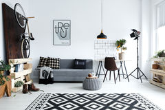 White living room with sofa. Hipster style, white living room with sofa, pouf, carpet, bike Stock Images