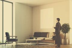 White living room, sofa, poster side, man. Businessman in a living room interior with white walls, a wooden floor, a sofa and a vertical poster. Loft windows and Stock Photos