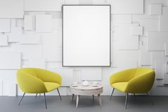 White living room, yellow armchairs and poster. White living room interior with yellow armchairs standing near a round coffee table with and a framed vertical Royalty Free Stock Photography