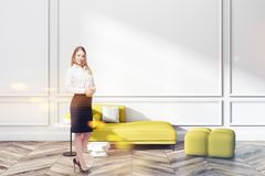 White living room, yellow sofa and poster, woman royalty free stock photography