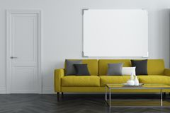 White living room, yellow sofa. White living room interior with a concrete floor, a long green sofa with colored cushions on it and a coffee table. A horizontal Stock Photography
