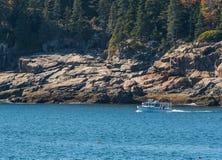 White Lobster Boat Along Rocky Maine Coast. Checks traps Stock Image