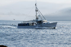 White lobster boat heads out to set traps with fogged in porcupi Royalty Free Stock Photos