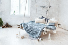 White loft interior in classic scandinavian style. Hanging bed suspended from the ceiling. Cozy large folded gray plaid Royalty Free Stock Photography