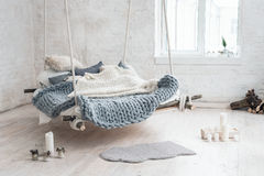 White loft interior in classic scandinavian style. Hanging bed suspended from the ceiling. Cozy large folded gray plaid Royalty Free Stock Photo
