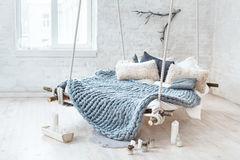White Loft Interior In Classic Scandinavian Style. Hanging Bed Suspended From The Ceiling. Cozy Large Folded Gray Plaid