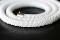 White long beaded necklace on a dark background. Close up stock photo