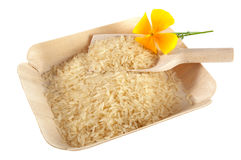 White long grain rice, scoop and yellow flower on bamboo tray Stock Image