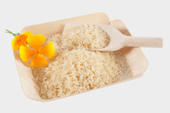 White long grain rice and yellow flowers on bamboo tray. White long grain rice, a wooden spoon and two yellow flowers on a bamboo tray Royalty Free Stock Image