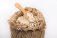 White long rice in burlap sack with wooden spoon Stock Photography