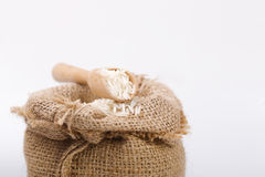 White long rice in burlap sack with wooden spoon Royalty Free Stock Photography