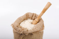 White long rice in burlap sack with wooden spoon Stock Photo
