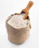 White long rice in a burlap sack and wooden spoon on white background Stock Photography