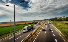 White Lorries passing - Highway Traffic. Through colorful Landscape royalty free stock image